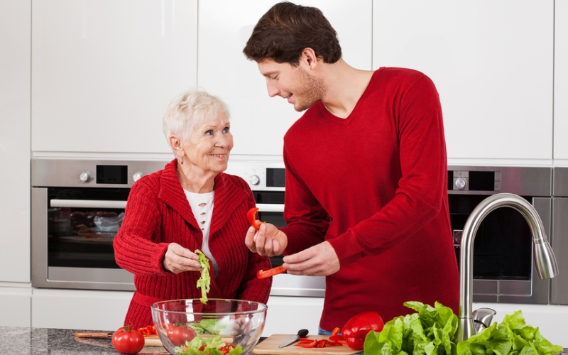 Adult son and elderly mother making together healthy salad